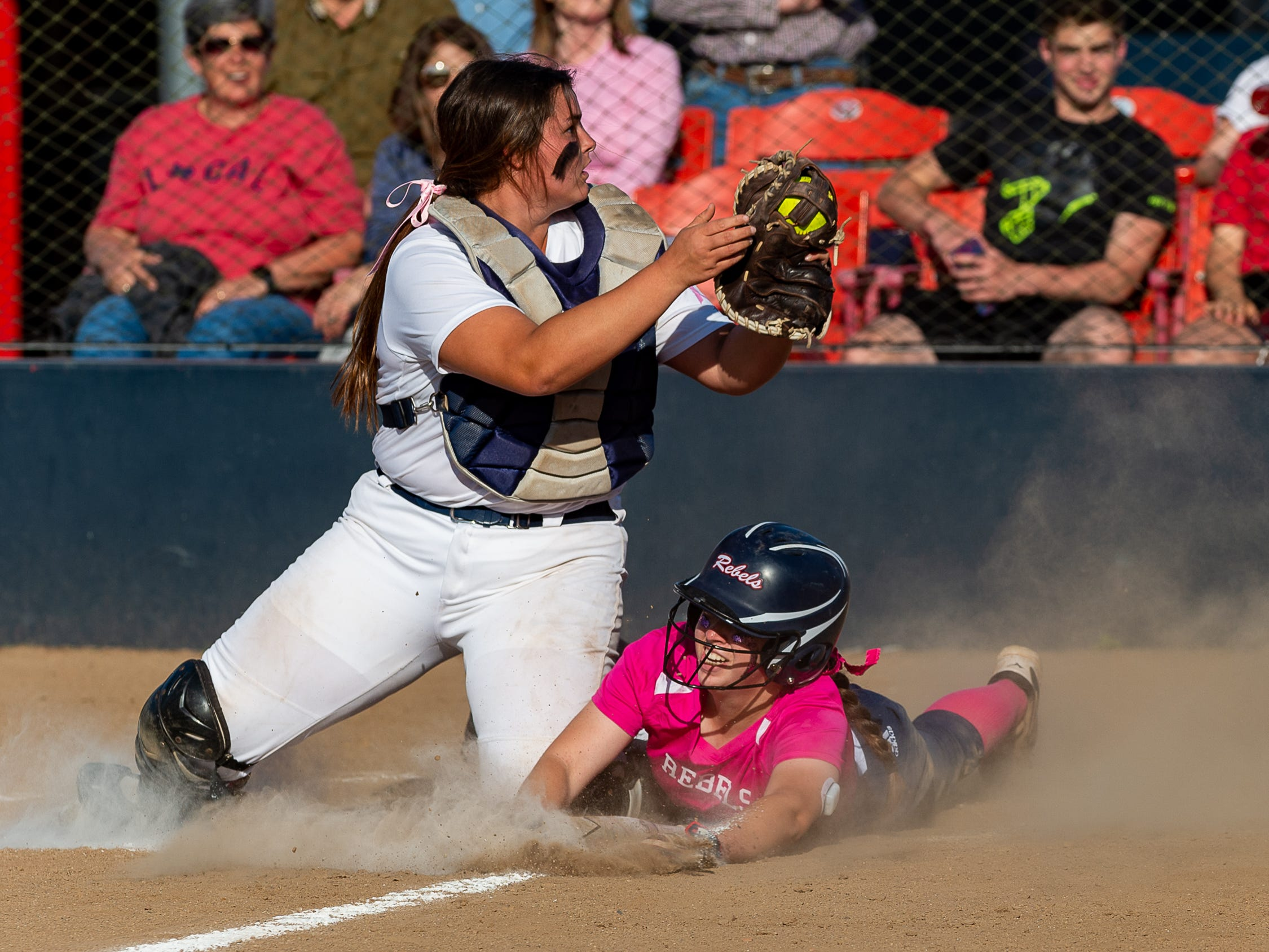 Rebels Olivia Edrey slides into home as Cougars catcher Hannah Parker lays down the tag as Teurlings Catholic host St Thomas More Softball. Tuesday, April 2, 2019.