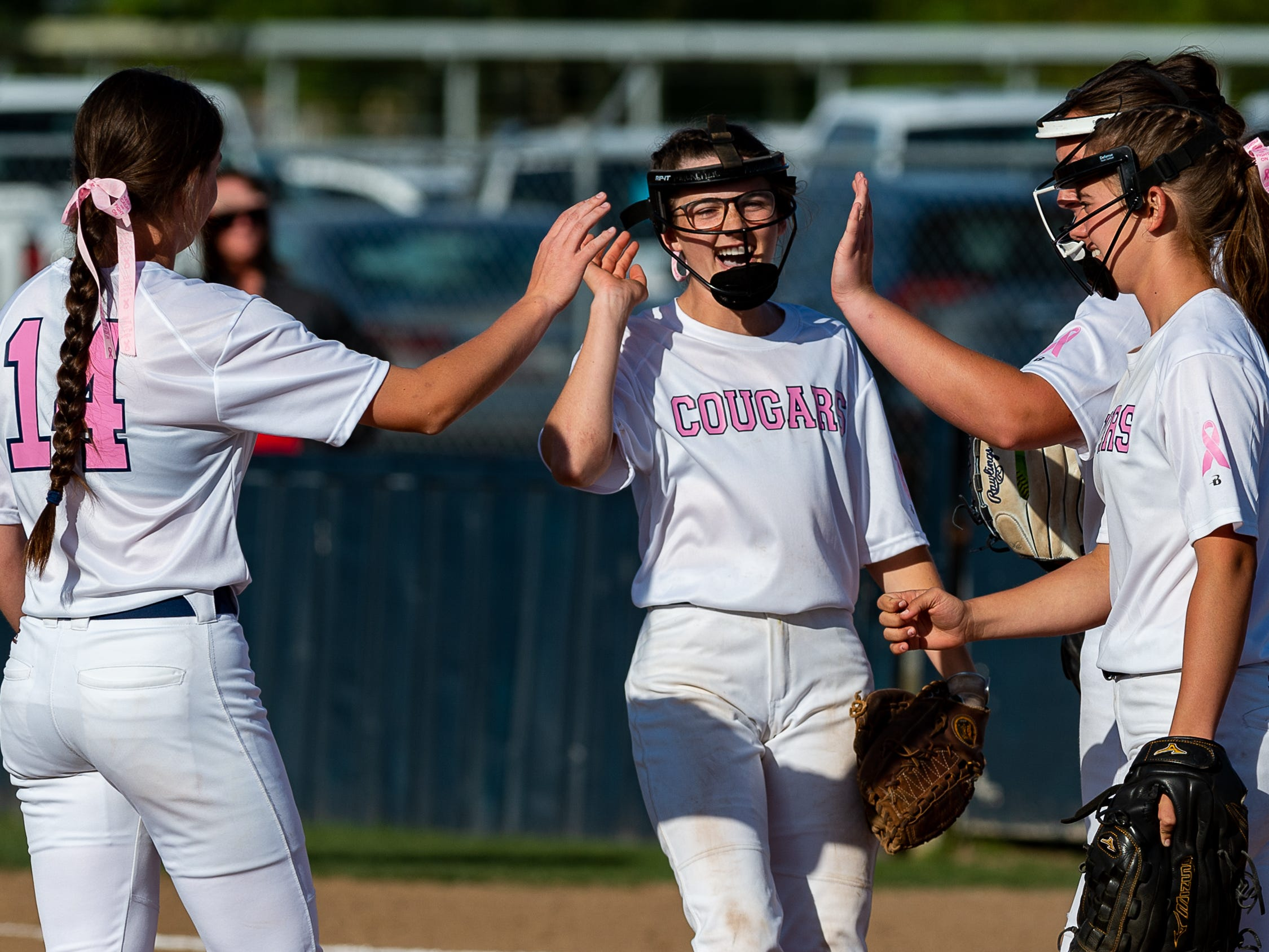 Cougars infielders celebrate as Teurlings Catholic host St Thomas More Softball. Tuesday, April 2, 2019.