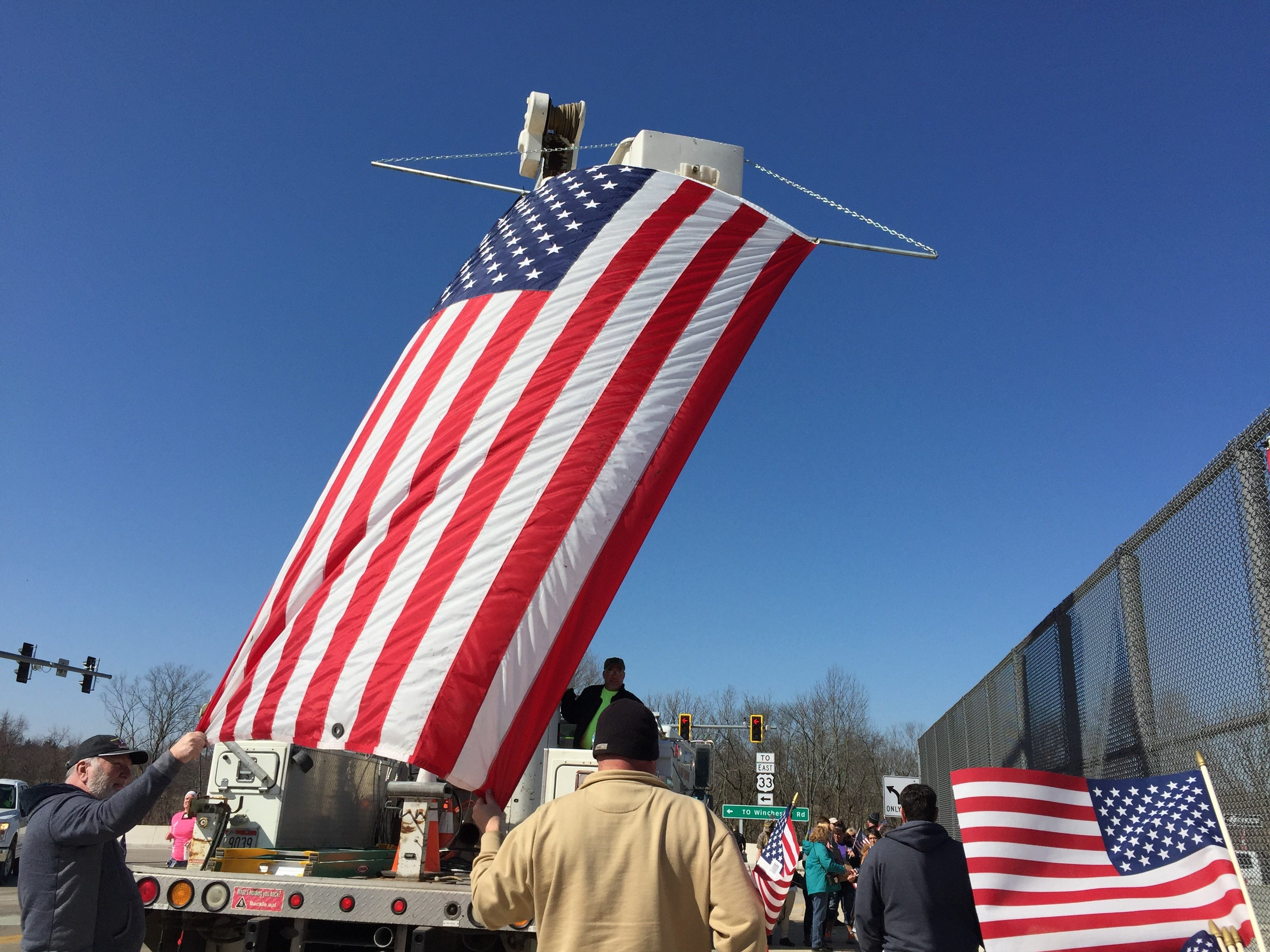 Over 100 people gather on the U.S. 33 overpass in Carroll, Wednesday for the U.S. Army Sgt. Joseph Collette procession.