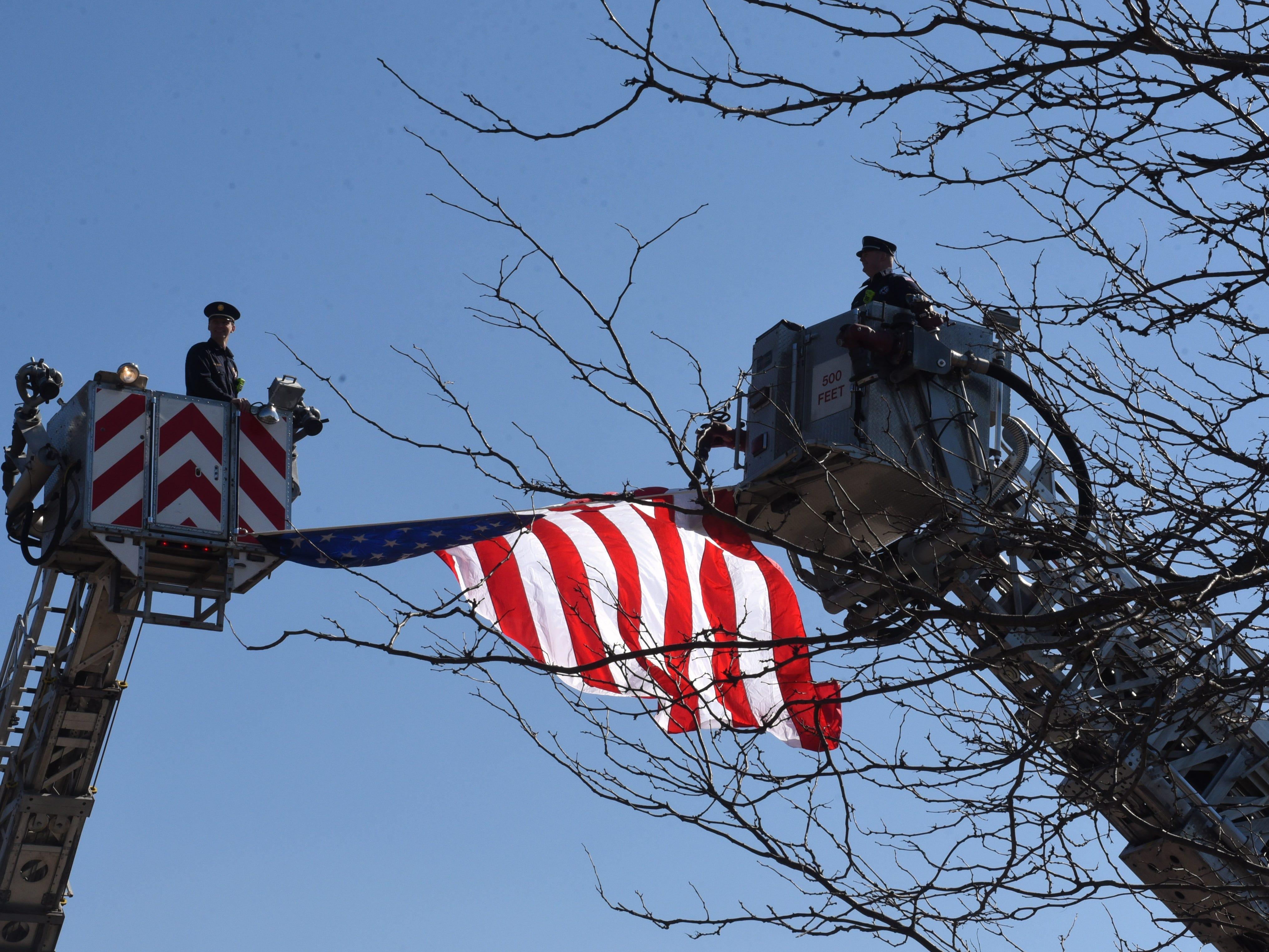 Two Lancaster Fire Department ladder trucks raise a flag over Main Street.