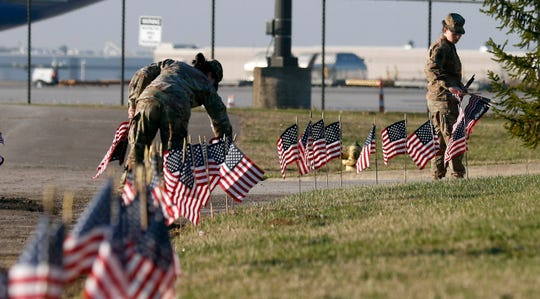 Military personnel place American flags along the roads at Rickenbacker International Airport Wednesday, April 3, 2019, in Columbus. Hundreds of flags lined the roads around the airport the mark the return of the body of Sgt. Joseph Collette.