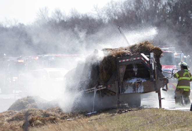 A fire smolders in hay on a flatbed trailer on northbound US-23 north of Silver Lake Road Wednesday, April 3, 2019, causing the shutdown of that side of the freeway for miles.