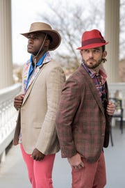 "Model Aaron Thornton, left, wears a tan linen Calvin Klein sport coat ($178), multi print Bugatchi shirt ($179), royal Bugatchi polo shirt ($89.50), coral ""suede"" Peter Miller jeans ($149), with a tan UV protector Stetson hat ($65) during a Kentucky Derby fashion shoot with stylist Jo Ross at Churchill Downs. Model Josh Frank wears a brown/coral plaid Peter Miller sport coat ($495), plaid Fact Face shirt ($65), rosey coral Trash Nouveau polo ($39); brick linen Ballin pants ($195), and a brick Stacey Adams straw hat ($40). March 28, 2019"