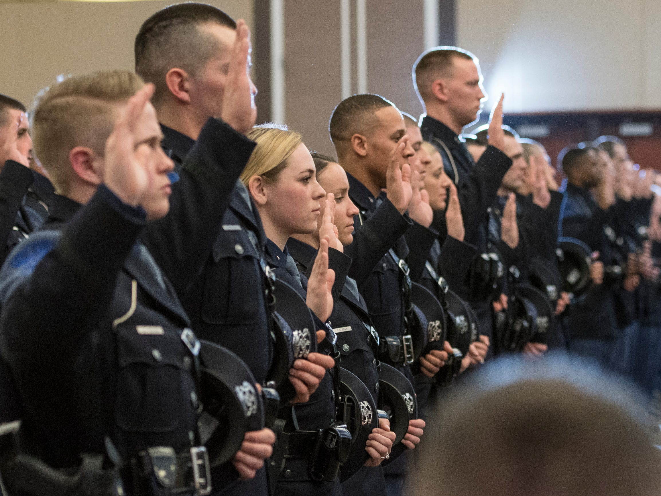 Members of the 135th Trooper Recruit School take the Oath of Office Wednesday, April 3, 2019, during the 135th Michigan State Police Trooper Recruit School graduation at the Lansing Center in downtown Lansing.  101 troopers earned their badges.