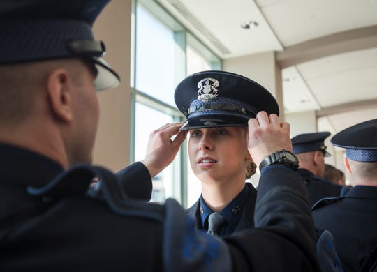 135th Trooper Recruit School trooper Kyle Grubbs assists classmate Conner Grosterffon with her lid Wednesday, April 3, 2019, before the 135th Michigan State Police Trooper Recruit School graduation at the Lansing Center in downtown Lansing.