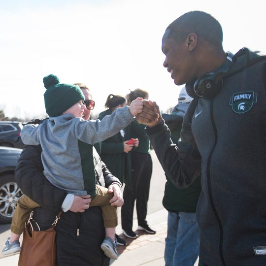 Michigan State point guard Cassius Winston fist bumps a young fan early Wednesday evening, April 3, 2019, as the Spartans head for the airport for Minneapolis from the Breslin Center.