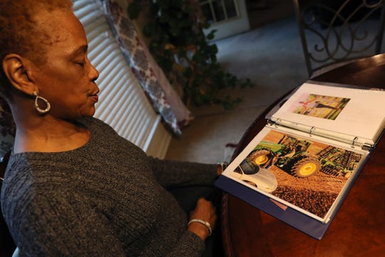 Everlyn Bryant, looks through old photos of her family on their farm, from their home in Pine Bluff, Arkansas, on Thursday, Feb. 14, 2019.