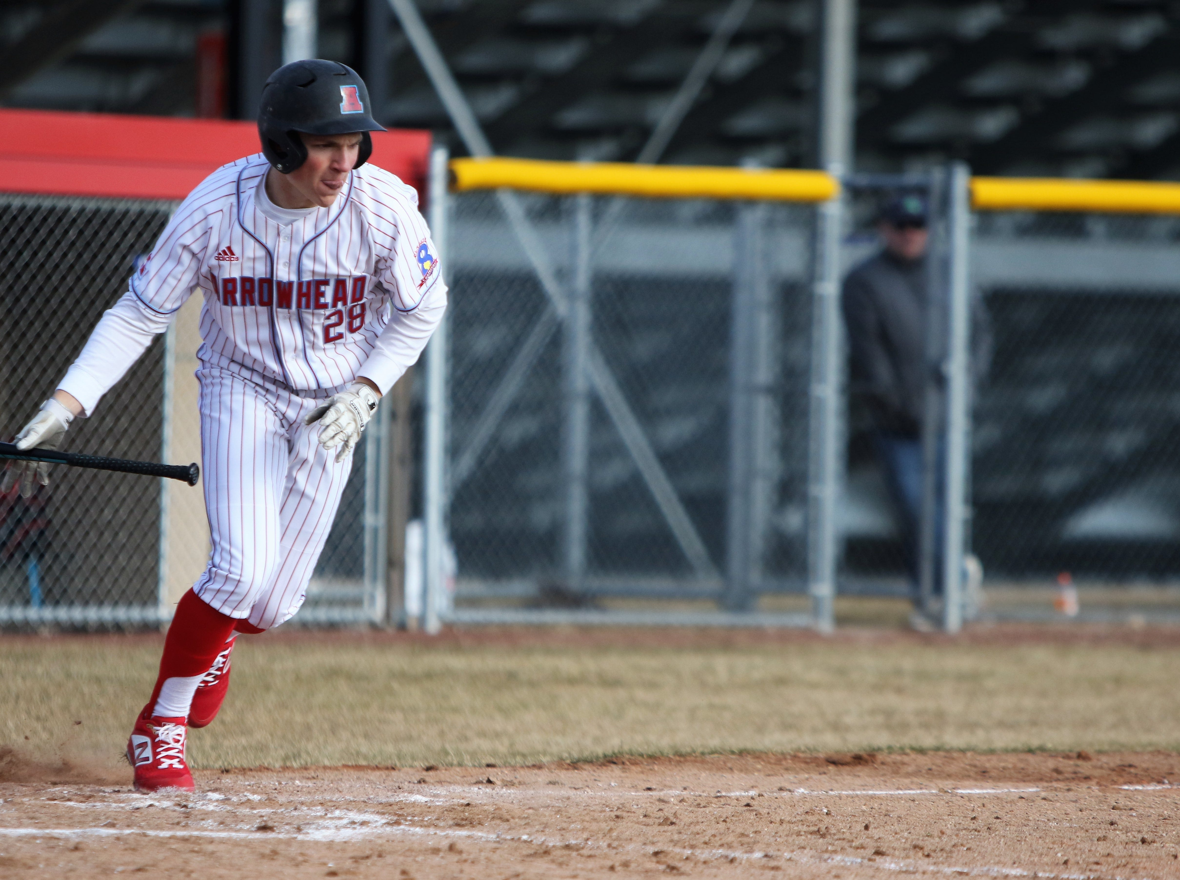 Tyler Loebel takes off toward first base after dropping down a bunt against Catholic Memorial on April 2, 2019.