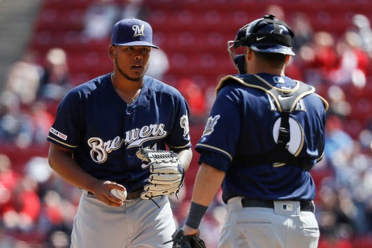 Brewers starting pitcher Freddy Peralta and catcher Manny Pina discuss what pitch they want to throw to the Reds' Yasiel Puig with the count at 2-2 during the bottom of the eighth inning Wednesday.