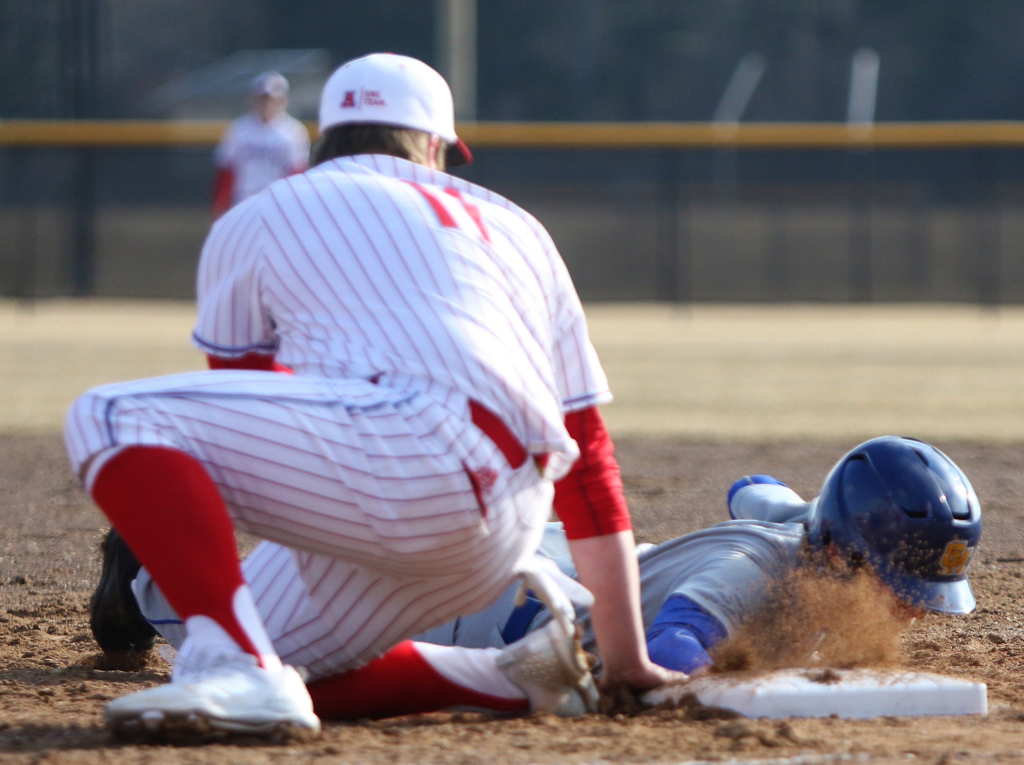 Catholic Memorial freshman Rory Fox dives safely into first base before Arrowhead's Tyler LaMack can apply the tag during a game on April 2, 2019.