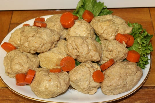 Gefilte fish are topped with sliced carrots for serving.