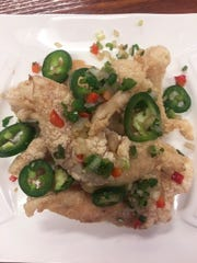 Freshly fried salted whitefish fillets are topped with bell peppers and jalapeños.