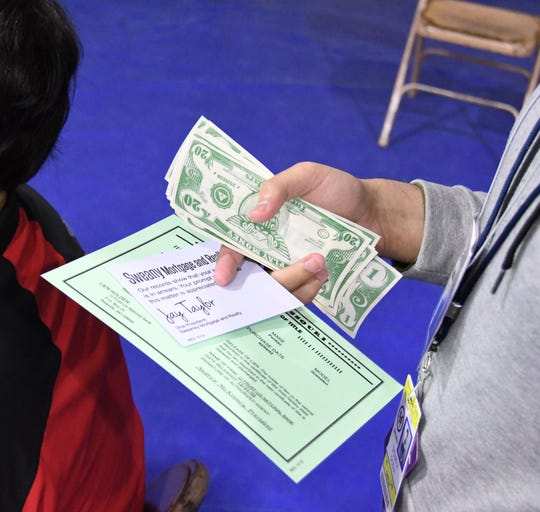 A Mountain Home student holds a handful of cash and a late payment notice while waiting to pay his house payment Wednesday at the poverty simulation held at Mountain Home High School.