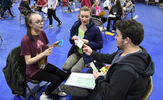 Sophomores (from left) Sarah Grace Curtis, Eloise Darracq and Nathanael Edington discuss their household's finances Wednesday during the poverty simulation at Mountain Home High School.