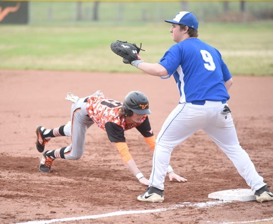 Viola's Carson Guffey dives back into first base during a recent game.