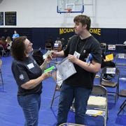 Sophomore Tony Street is robbed at gunpoint by Janie Austin during Wednesday's poverty simulation at Mountain Home High School.