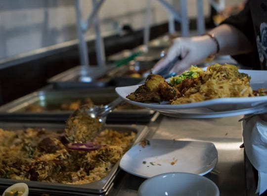 A customer at Little India restaurant in Monroe, La. loads a plate with food from the lunch buffet. The newly opened restaurant features a full menu of Indian cuisine and a lunch buffet from 11 a.m. - 2:30 p.m. Tuesday- Sunday.