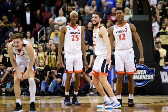 Virginia Cavaliers guard Ty Jerome (11) celebrates with forward Mamadi Diakite (25) and guard De'Andre Hunter (12) after the win over the Purdue Boilermakers in overtime on March 30, 2019, in Louisville, Ky.