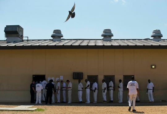 "In this June 18, 2015, file photo, prisoners stand in a crowded lunch line during a prison tour at Elmore Correctional Facility in Elmore, Ala. The Justice Department has determined that Alabama's prisons are violating the Constitution by failing to protect inmates from violence and sexual abuse and by housing them in unsafe and overcrowded facilities, according to a scathing report Wednesday, April 3, 2019, that described the problems as ""severe"" and ""systemic."""
