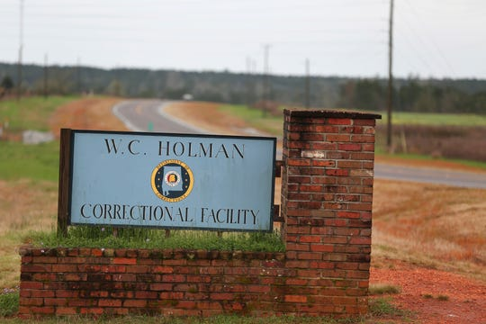 In this March 12, 2016 file photo, the sign to The William C. Holman Correctional Facility in Atmore, Ala., is displayed. The Justice Department has determined that Alabama's prisons are violating the Constitution by failing to protect inmates from violence and sexual abuse and by housing them in unsafe and overcrowded facilities, according to a scathing report.