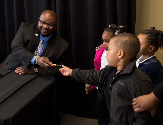 Benjamin Jones, CEO of Montgomery Community Action, gets a pen from students during a signing ceremony at Alabama State University in Montgomery, Ala., on Wednesday, April 3, 2019.