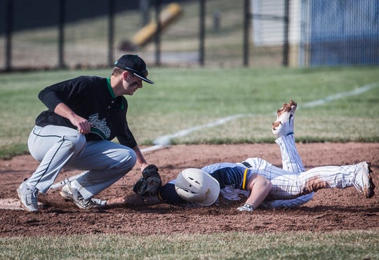 Yorktown's Dom Cantanzarite tags out Delta's Logan Drown at third base during their game at Delta High School Tuesday, April 2, 2019.