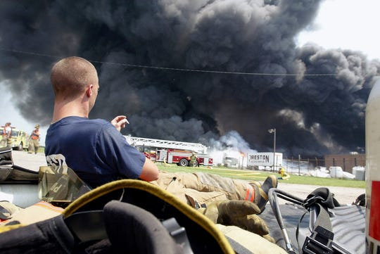 A Yorktown firefighter rests as his comrades battle a stubborn fire at the CR3 tire and rubber recycling facility in August of 2003.