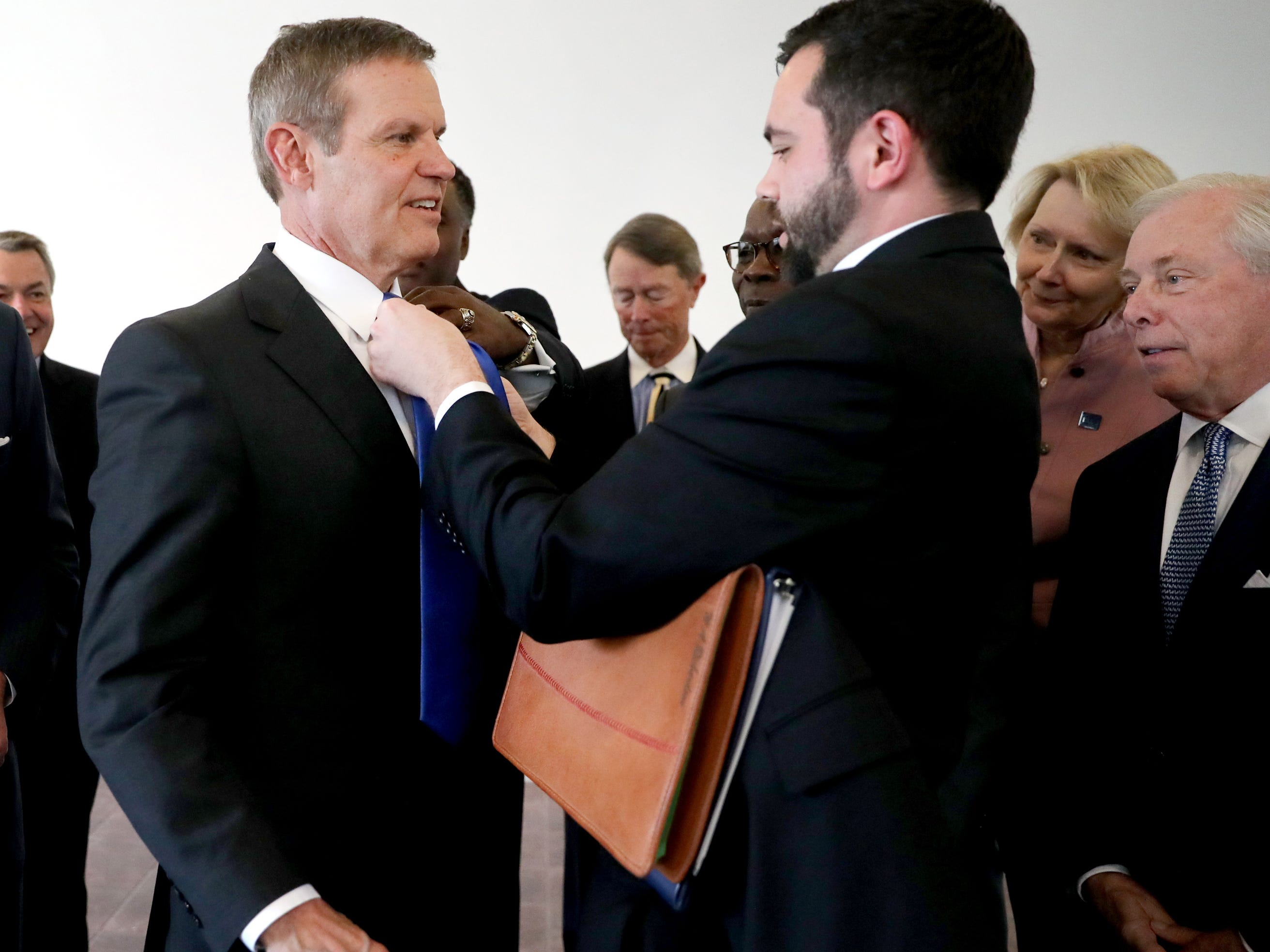 Alec Richardson, a personal Aide to the Governor changes out Tennessee Governor Bill Lee's tie to an MTSU blue tie before he has his picture taken with the MTSU board of trustees , on Wednesday April 3, 2019.  Lee also spoke at MTSU's program recognizing the Siemens' grant to MTSU's Mechatronics Engineering program, on Wednesday April 3, 2019.