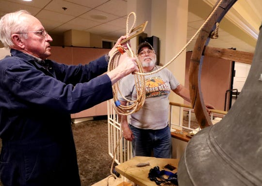 John Sallee, left, and Ron Lindsey, right, install the old bell that was once located in the former First United Methodist Church site in downtown Murfreesboro at the new church site on Thompson Lane, on Tuesday April 2, 2019.