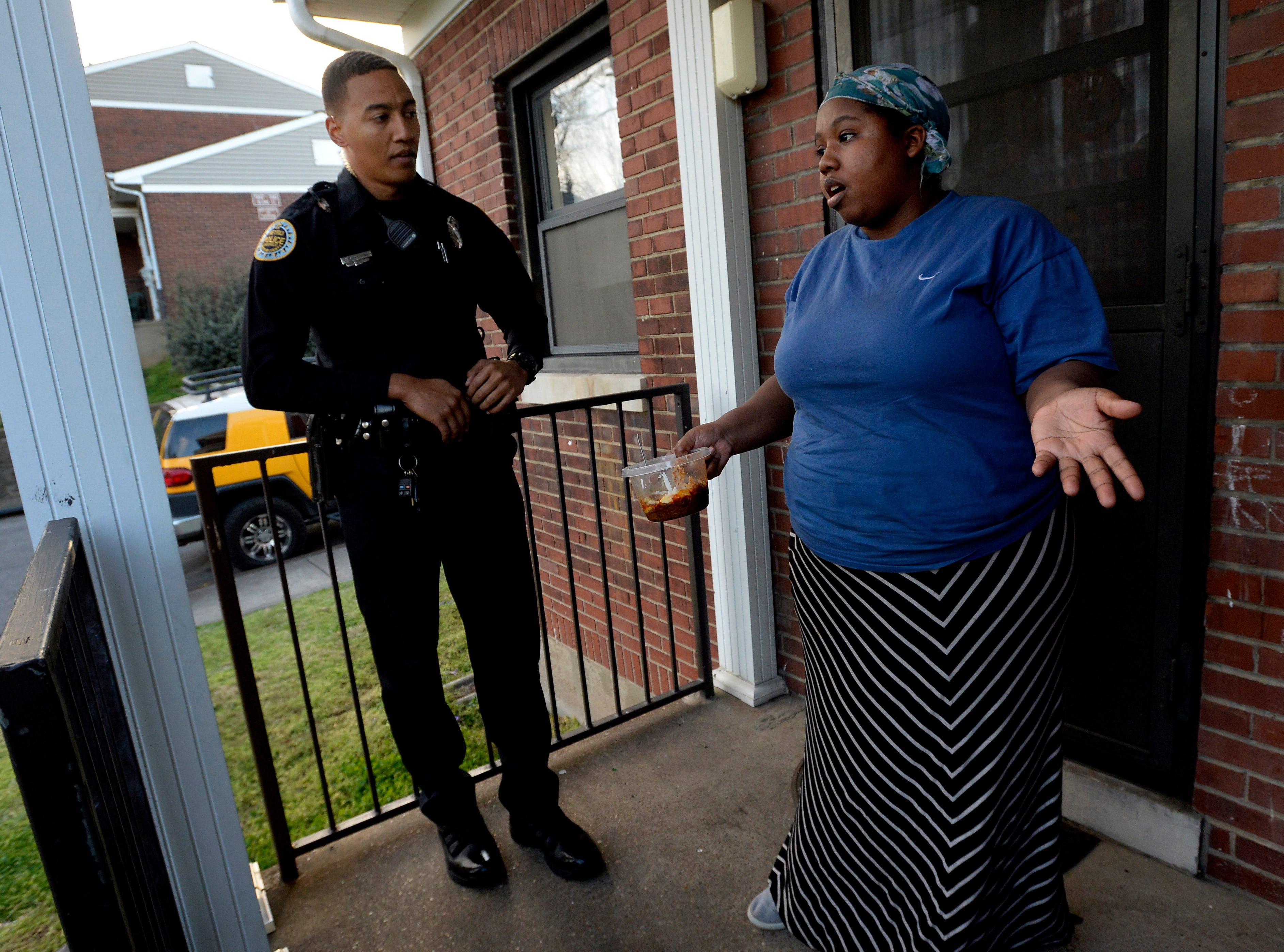 """Metro Nashville police officer Chris Dickerson listens to Lashandra Fuller, 30, as he spends time talking with her on Monday, April 1, 2019 in Nashville, Tenn. During the """"fixed post"""" time of his shift, Dickerson spends about 30 minutes in different areas of the north precinct visiting with people in the neighborhood."""