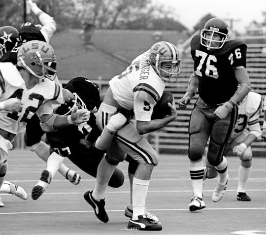 Vanderbilt big senior defensive end Dennis Harrison (77) pulls LSU quarterback Steve Ensminger (5) down. The Commodores lost 28-15 in Nashville Oct. 8, 1977.