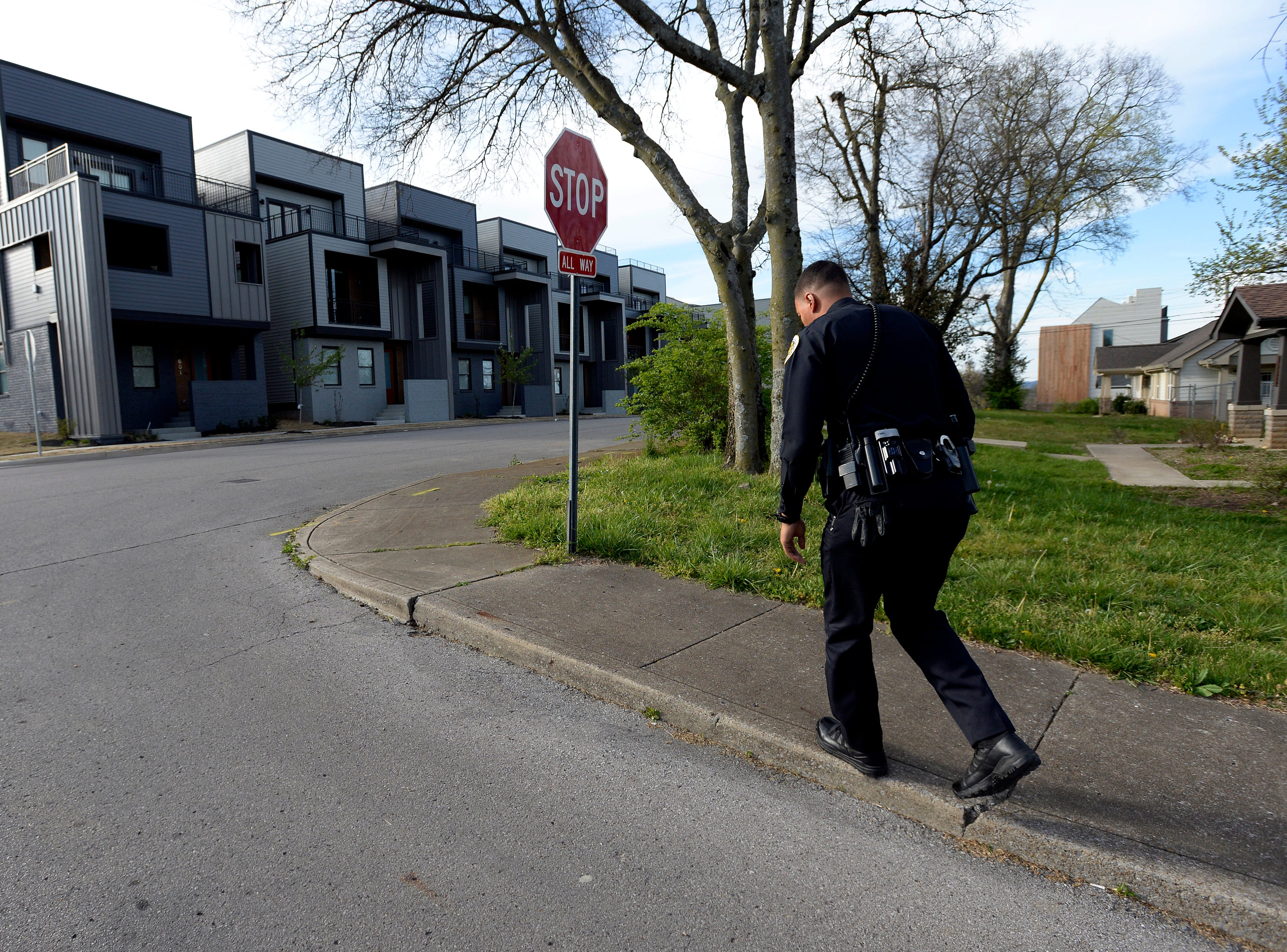 """Metro Nashville police officer Chris Dickerson walks to visit residents at their homes along 27th Avenue North on Monday, April 1, 2019 in Nashville, Tenn. During the """"fixed post"""" time of his shift, Dickerson spends about 30 minutes in different areas of the north precinct visiting with people in the neighborhood."""