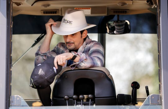 Country music star Brad Paisley puts on a hard hat shaped like a cowboy hat as he sits at the controls of a backhoe after digging a hole to break ground for The Store, a free grocery store for people in need, on April 3, 2019, in Nashville.