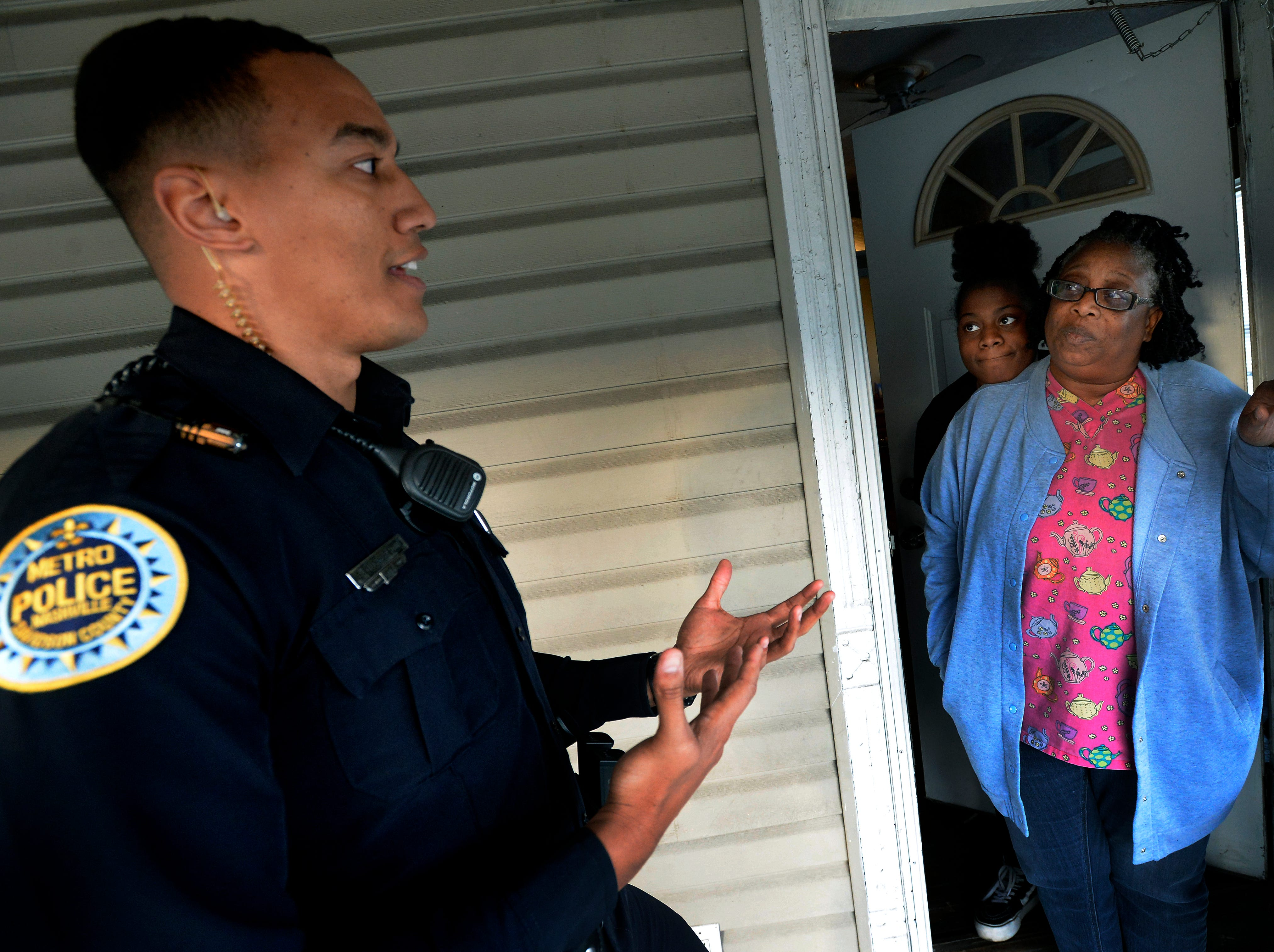 """Metro Nashville police officer Chris Dickerson spends time talking with Regina Scruggs and Athyiah Word at their home on Monday, April 1, 2019 in Nashville, Tenn. During the """"fixed post"""" time of his shift, Dickerson spends about 30 minutes in different areas of the north precinct visiting with people in the neighborhood."""
