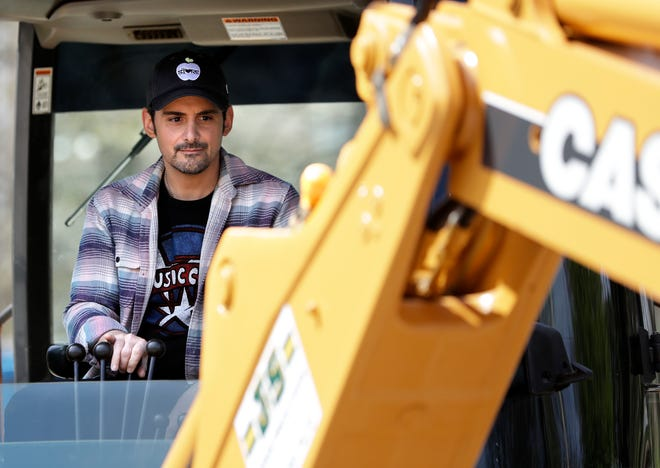 Country music star Brad Paisley operates a backhoe as he breaks ground for The Store, a free grocery store for people in need, on April 3, 2019.