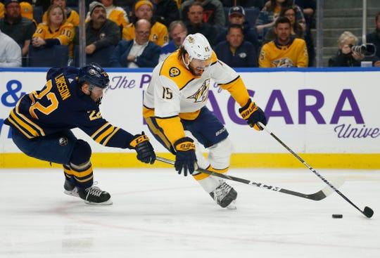 Buffalo Sabres forward Johan Larsson (22) stick checks Nashville Predators forward Craig Smith (15) during the second period of an NHL hockey game Tuesday, April 2, 2019, in Buffalo, N.Y.