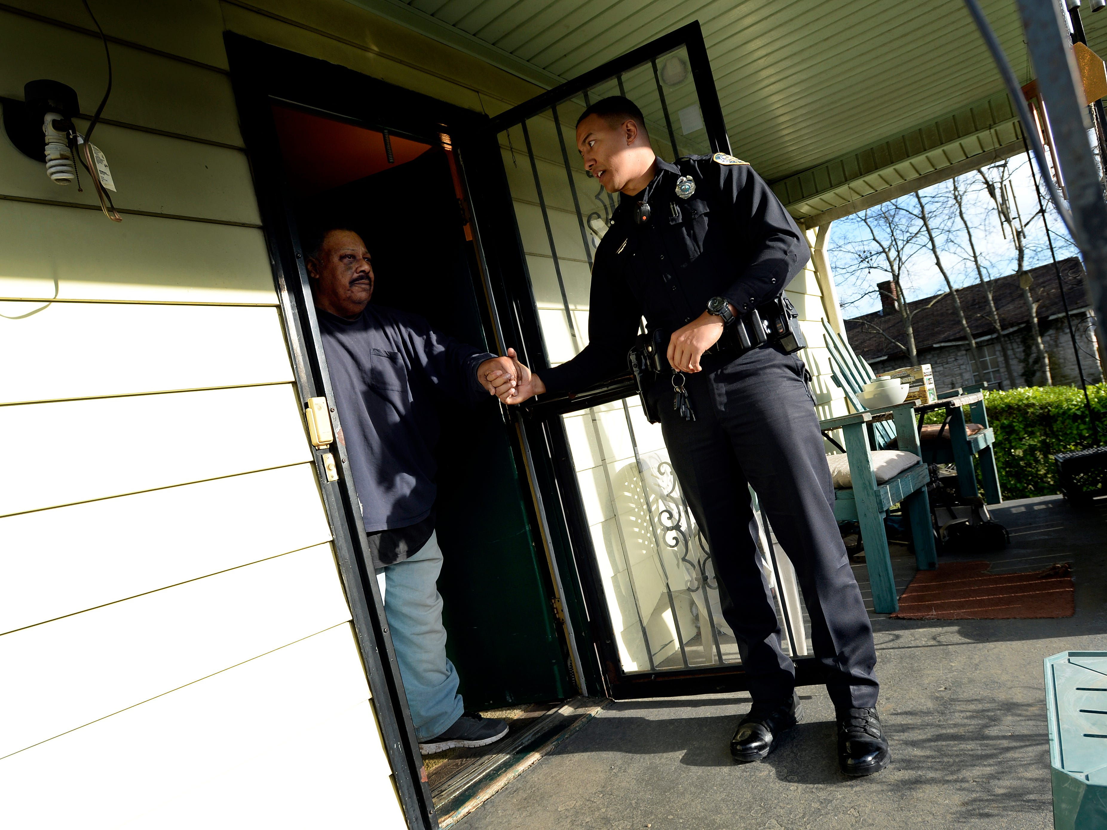 """Metro Nashville police officer Chris Dickerson shakes hands with Michael Taylor, 67, after spending time talking with him on Monday, April 1, 2019 in Nashville, Tenn. During the """"fixed post"""" time of his shift, Dickerson spends about 30 minutes in different areas of the north precinct visiting with people in the neighborhood."""