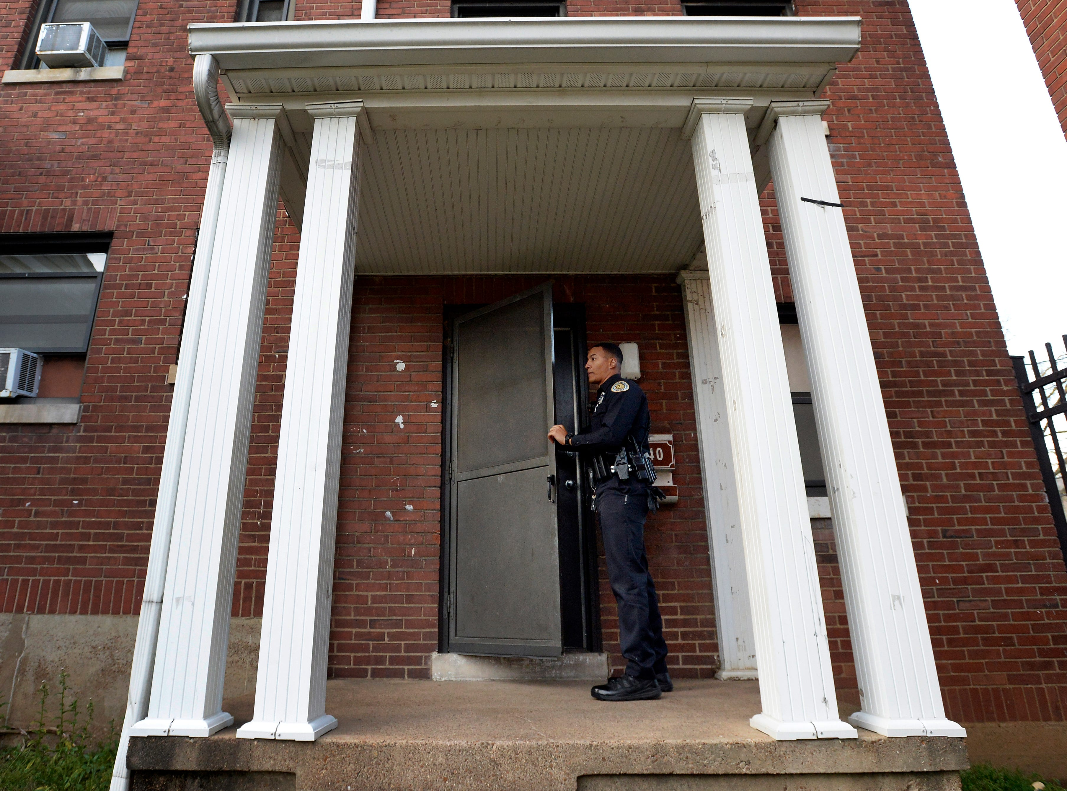 """Metro Nashville police officer Chris Dickerson knocks on an apartment door hoping to talk with the resident on Monday, April 1, 2019 in Nashville, Tenn. During the """"fixed post"""" time of his shift, Dickerson spends about 30 minutes in different areas of the north precinct visiting with people in the neighborhood."""