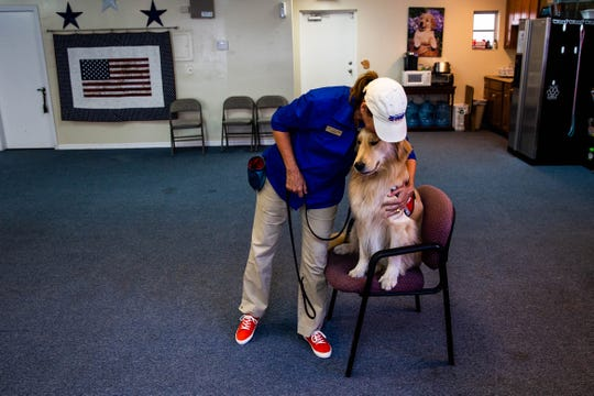 Volunteer and senior handler Karen Rakow hugs Jeffrey, a 2-year-old golden retriever, after his training session at the Golden PAWS Assistance Dogs facility in Naples on Wednesday, April 3, 2019.