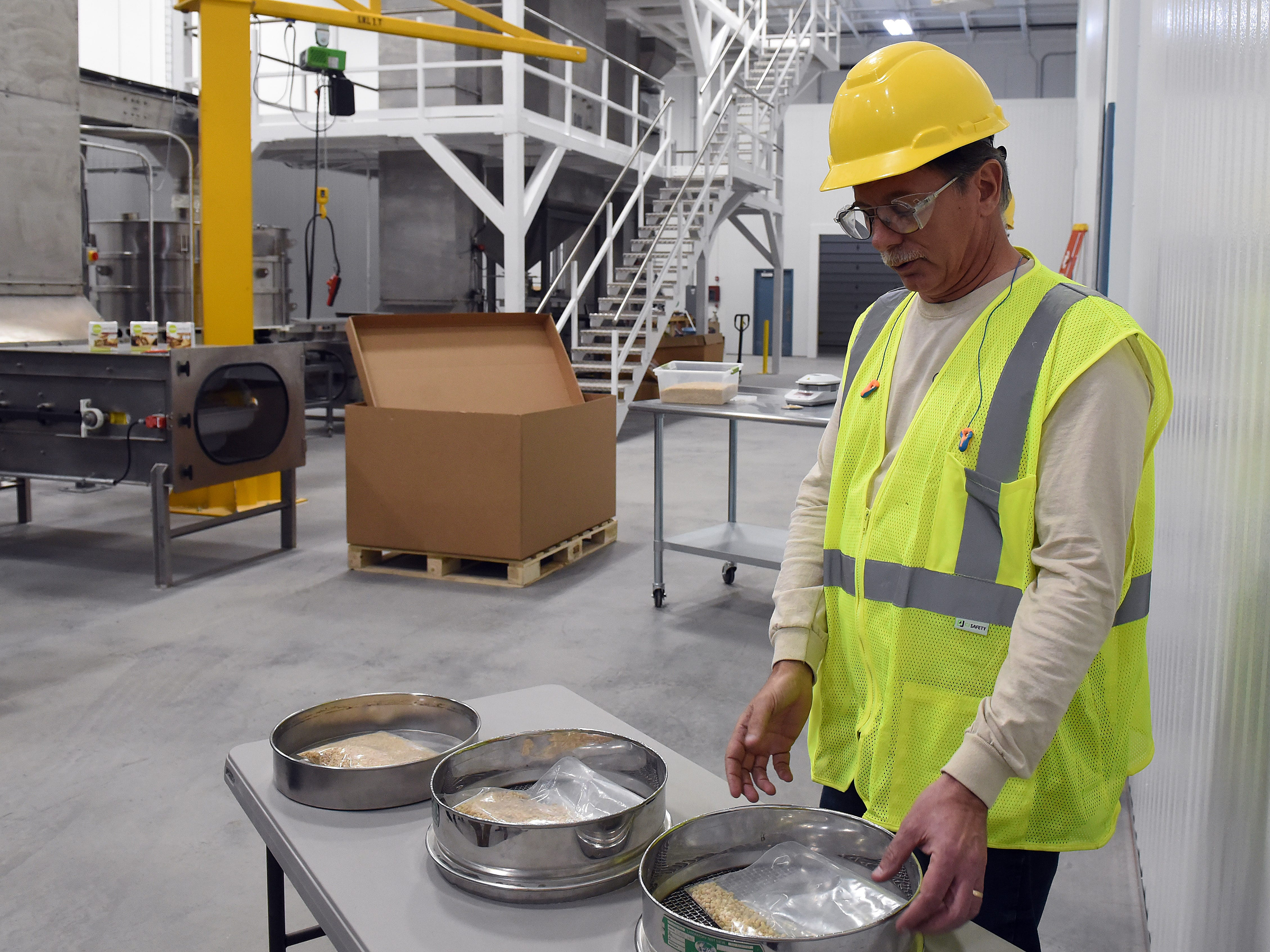 Brad McCullough demonstrates the sorting and shifting process at GB Food. The company, a partnership of companies in the United Kingdom and China, uses a non-GMO soy protein as the key ingredient in its food.