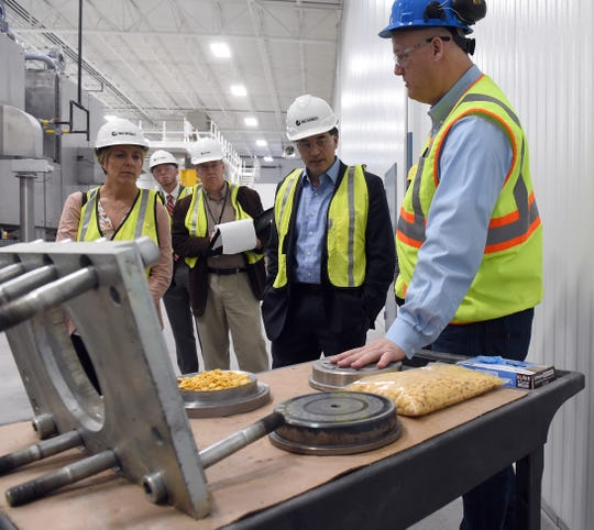GB Food plant director Troy Brunn shows guest U.S. Rep. Troy Balderson an example of extruded cereal flakes made from corn.