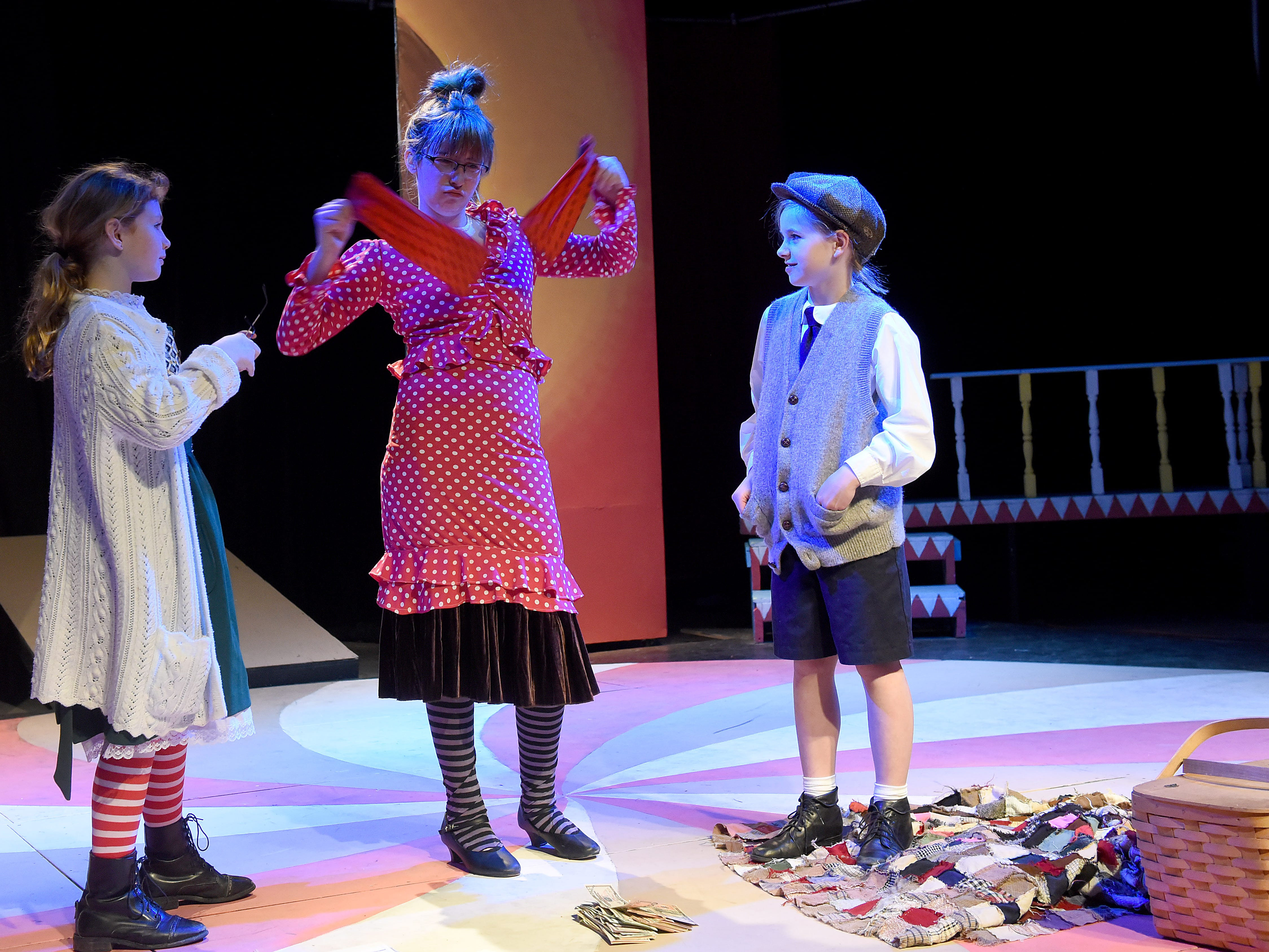 Portraying cruel aunts, Jennalyn Shafer and Avamarie Hedrick harass their nephew James, portrayed by Isabelle Tracy, during a rehearsal for Weathervane Young Artists' Repertory Theatre's production of James and the Giant Peach. The musical, based on the novel by Roald Dahl, begins on Friday, April 5.