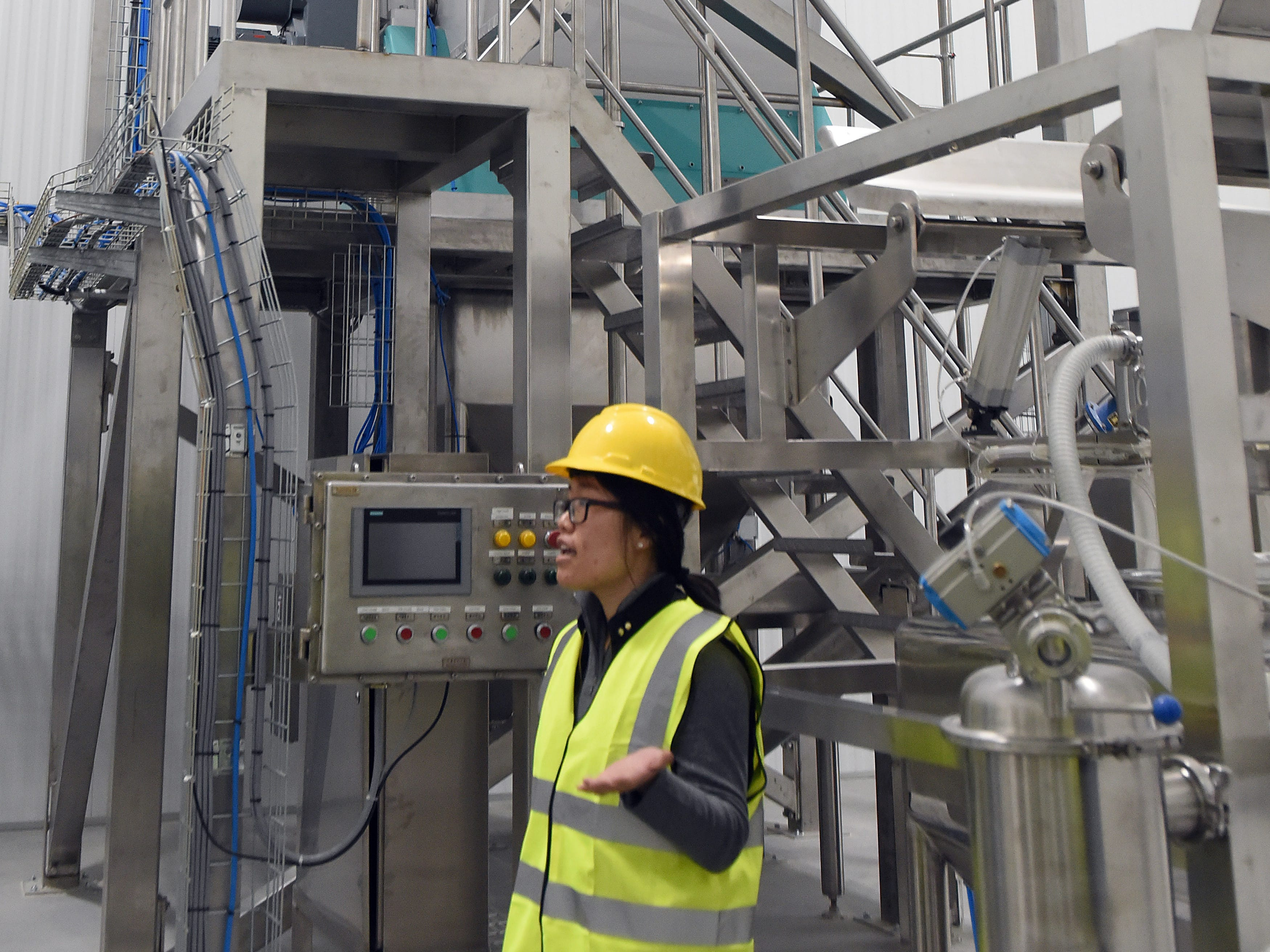 Gushen America logistics coordinator Emily Ma in front of mixer at GB Food in Heath. The company, a partnership of companies in the United Kingdom and China, uses a non-GMO soy protein as the key ingredient in its food.