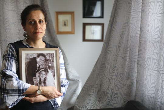 Poopak Mohajer holds a picture of her brother, Reza Mohajer and sister-in-law, Elham Maddadi. Mohajer, who moved to the U.S. in 2001, from Iran, has been trying to obtain permission for her brother to do the same since 2004.  Last year it looked as if it it would finally happen after countless letters and fees.  Then the ban started for Iran and four other countries. Tuesday, April, 2, 2019