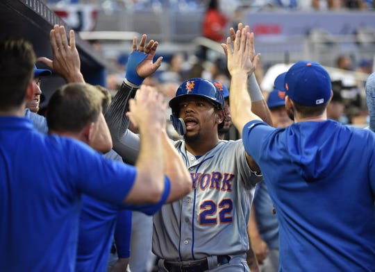 Apr 2, 2019; Miami, FL, USA; New York Mets first baseman Dominic Smith (22) is congratulated by teammates after scoring in the first inning against the Miami Marlins at Marlins Park.