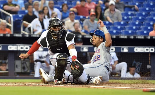 Apr 2, 2019; Miami, FL, USA; New York Mets first baseman Dominic Smith (22) slides into home plate to beat a throw to Miami Marlins catcher Jorge Alfaro (38) in the first inning at Marlins Park.