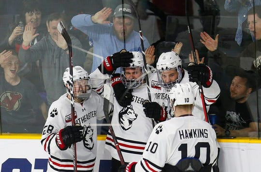 Northeastern's Liam Pecararo, second from left, celebrates his goal with teammates Zach Solow (28), Jeremy Davies (4) and Brandon Hawkins (10).