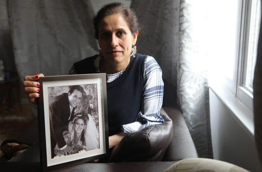 Poopak Mohajer holds a picture of her brother, Reza Mohajer and sister-in-law, Elham Maddadi. Mohajer, who moved to the U.S. in 2001, from Iran, has been trying to obtain permission for her brother to do the same since 2004. Last year it looked as if it it would finally happen after countless letters and fees. Then the ban started. Tuesday, April, 2, 2019