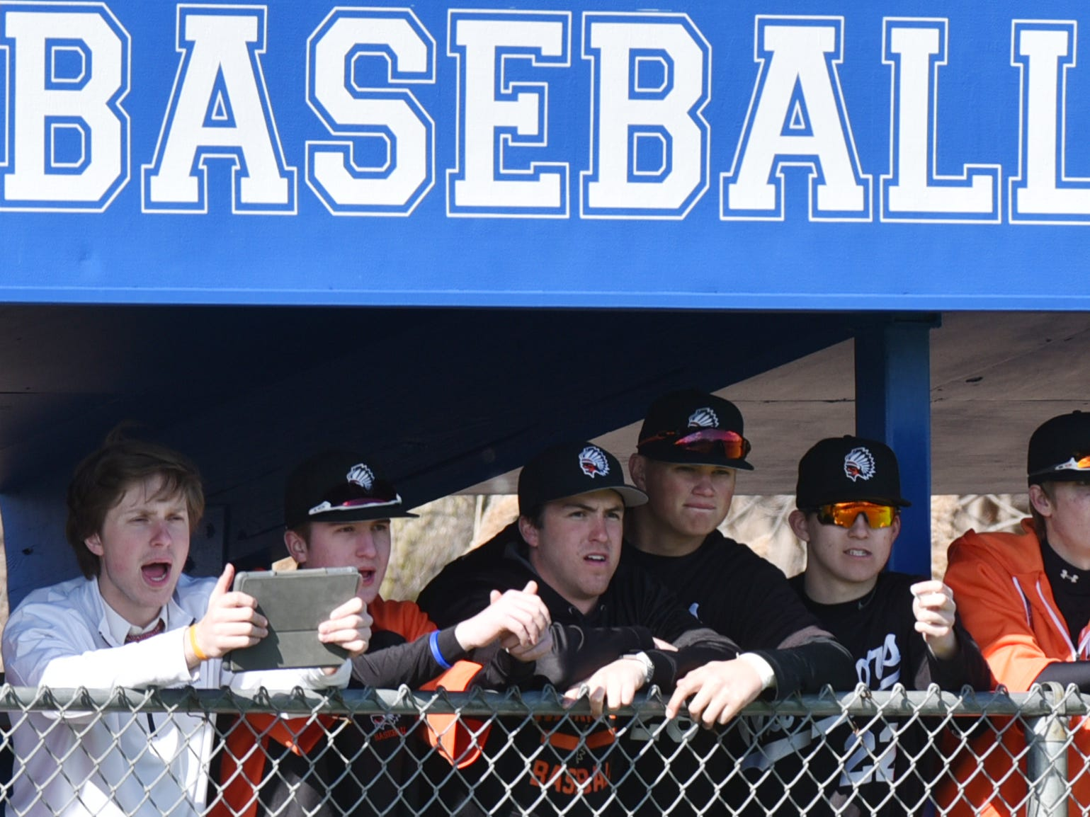 Brother Rice players watch the action from their dugout on April 3.