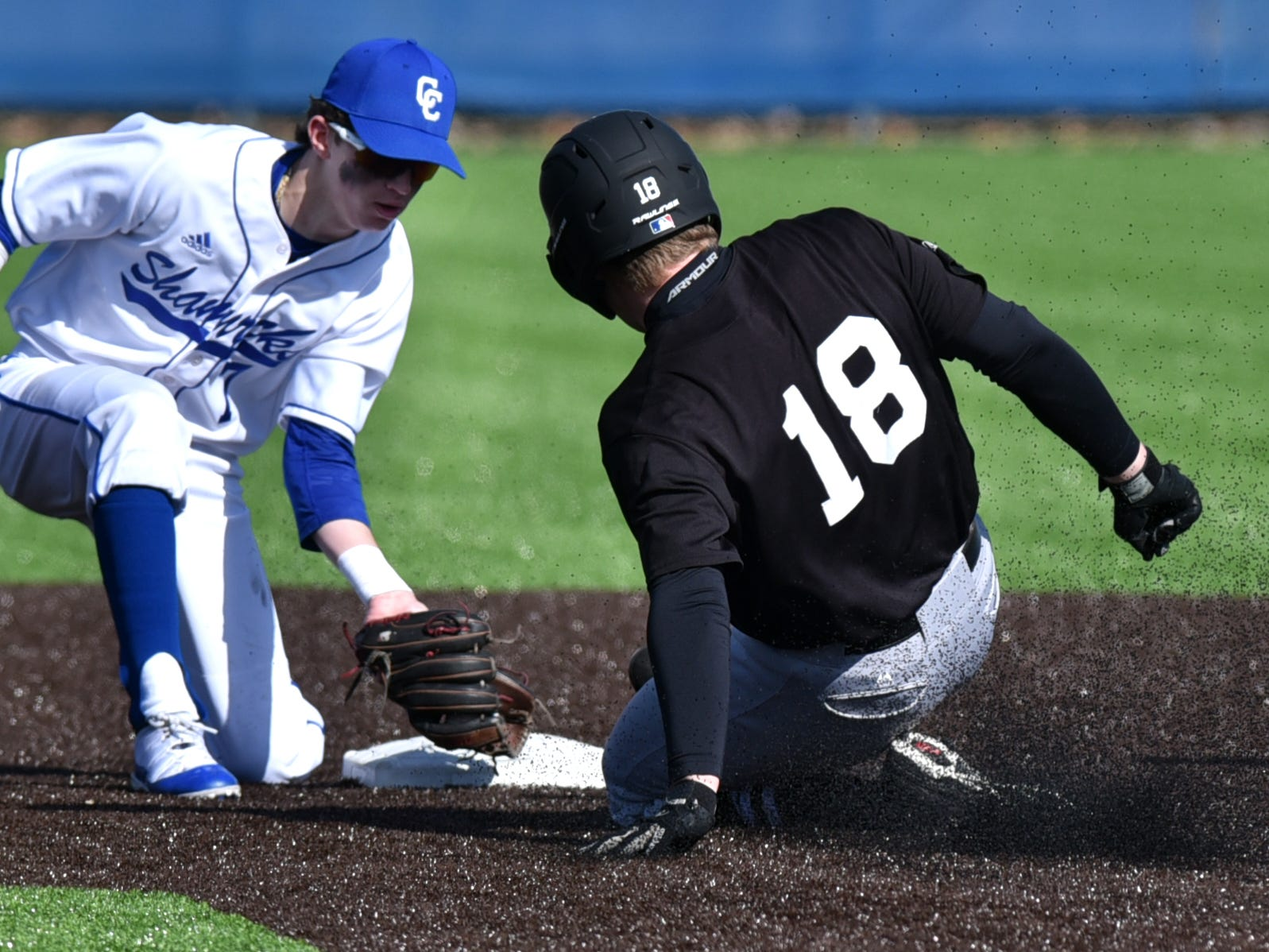 As he slides and throws up a cloud of rubber pellets from the artificial turf - Brother Rice's Sterling Hallman is met at second base by Detroit Cathlolic Central's Regan Paulina - and a tag.